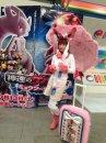 Feelinara | TV-Serie | Shoko Nakagawa als Feelinara in Pokémon Smash! vor einem Werbeplakat zum 16. Pokémon Kinofilm.